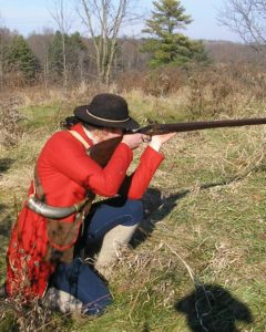 Soldier kneeling in scrub brush aiming gun