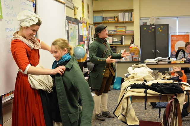 Students trying on 18th century soldier clothing