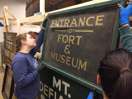 Tabitha and Persis, hanging the Entrance sign in the collections storage facility
