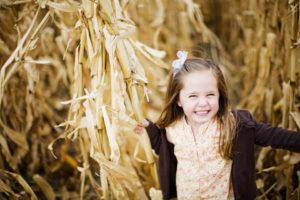 Little girl running through corn maze