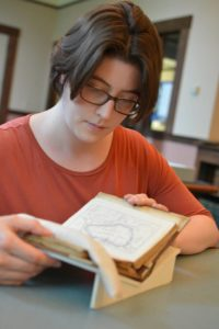 Anna Faherty, Edward W. Pell Graduate Fellow, reading one of Ella's travel diaries
