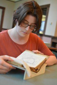 Anna Faherty, Edward W. Pell Graduate Fellow, reading one of Ella's travel diaries