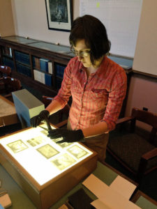 Miranda Peters arranges early 20th c. glass plate photo negatives on a light box