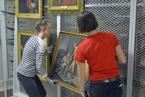 Margaret Staudter and Collections Manager, Miranda Peters, re-house a 19th c. painting of Ethan Allen