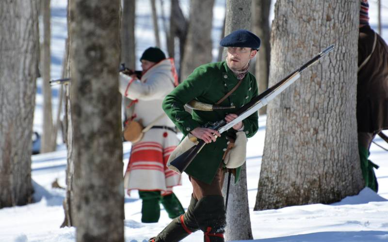 interpretive ranger in motion with musket in snow