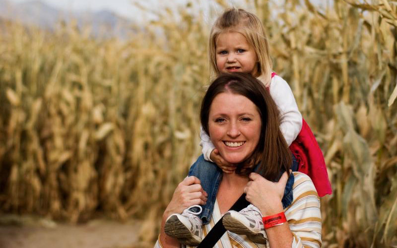 Woman carrying child on back in corn maze
