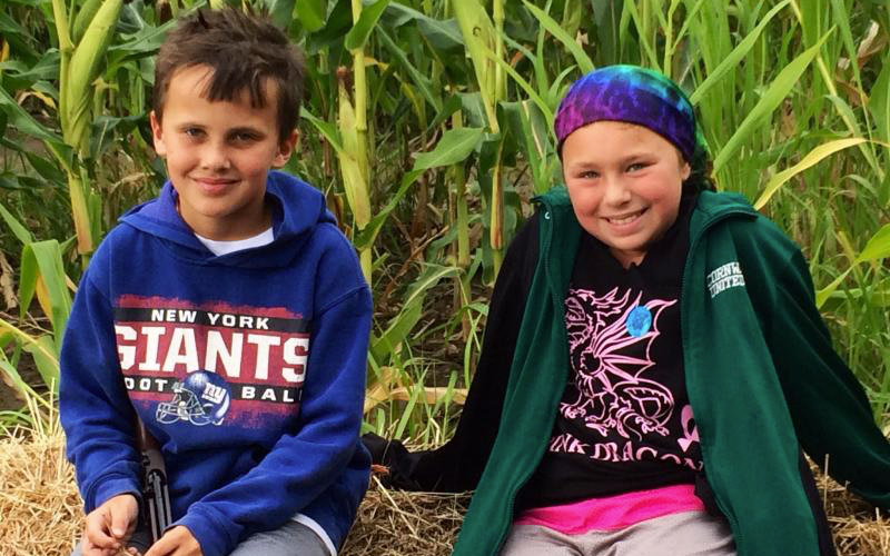 Two kids sitting on edge of corn maze