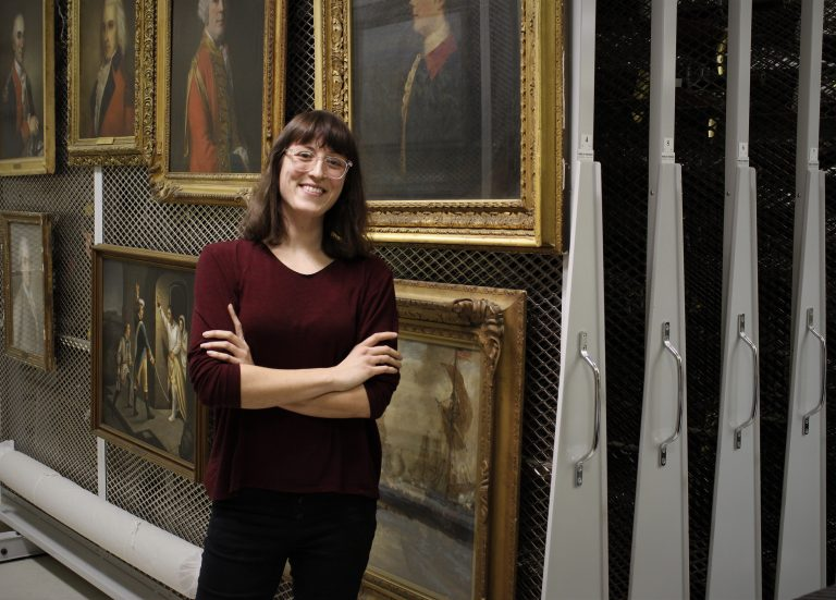 Miranda Peters standing in front of paintings