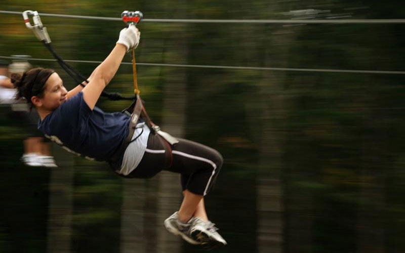 Girl on zip-line at the Adirondack Extreme Adventure Course