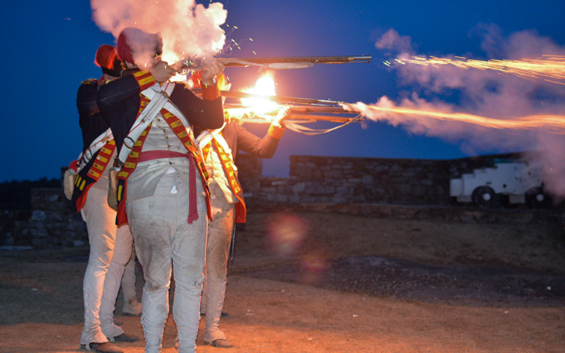 Re-enactors firing off muskets at night