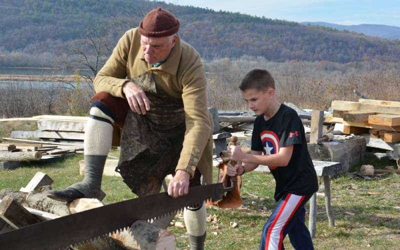 Soldier with boy using saw
