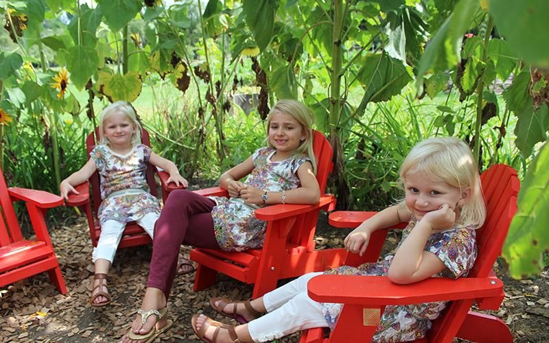 Girls sitting in Adirondack chairs in King's Garden