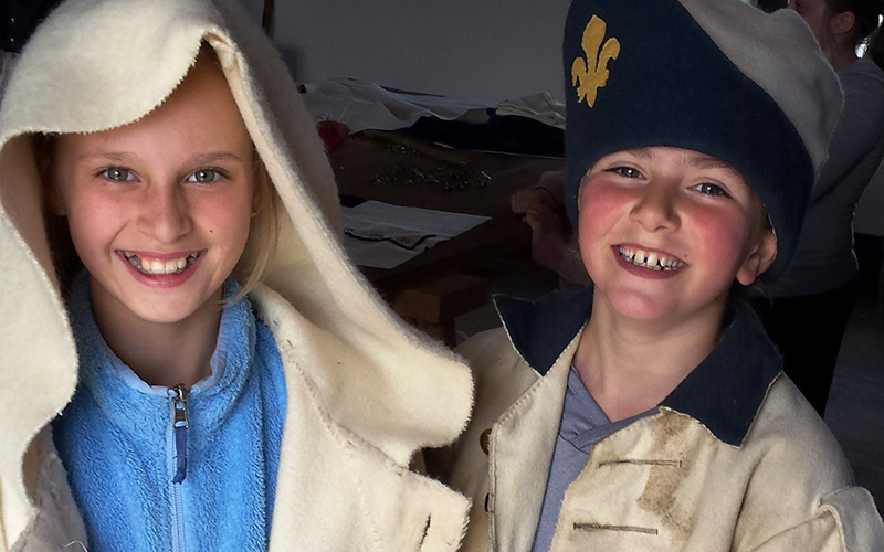 Kids dressed in period clothing Ccoat and hats)