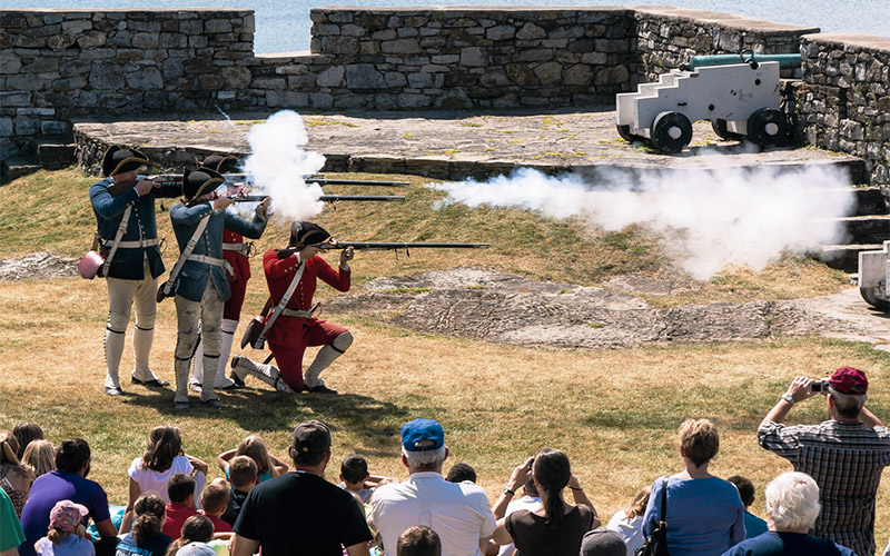Men firing rifles during battle reenactment
