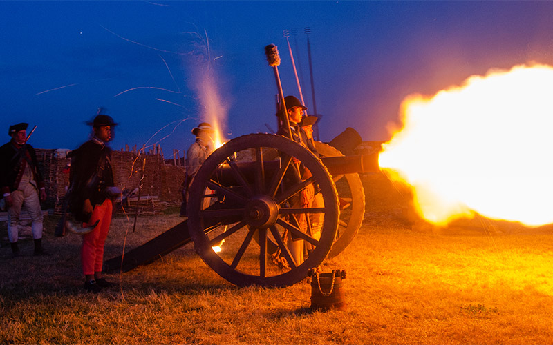 Men firing cannon at night