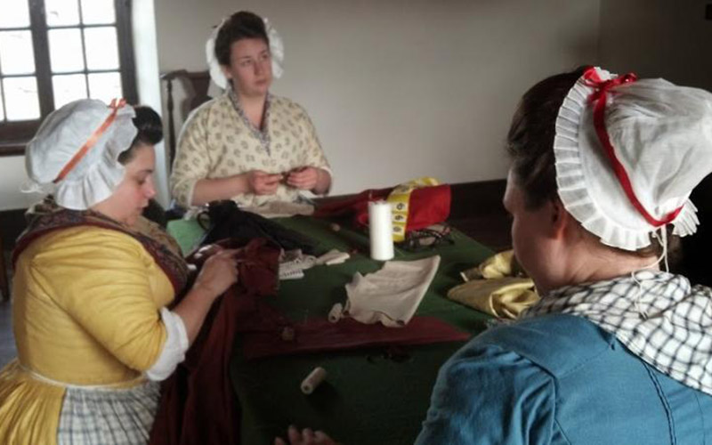 Women sitting at table mending clothing
