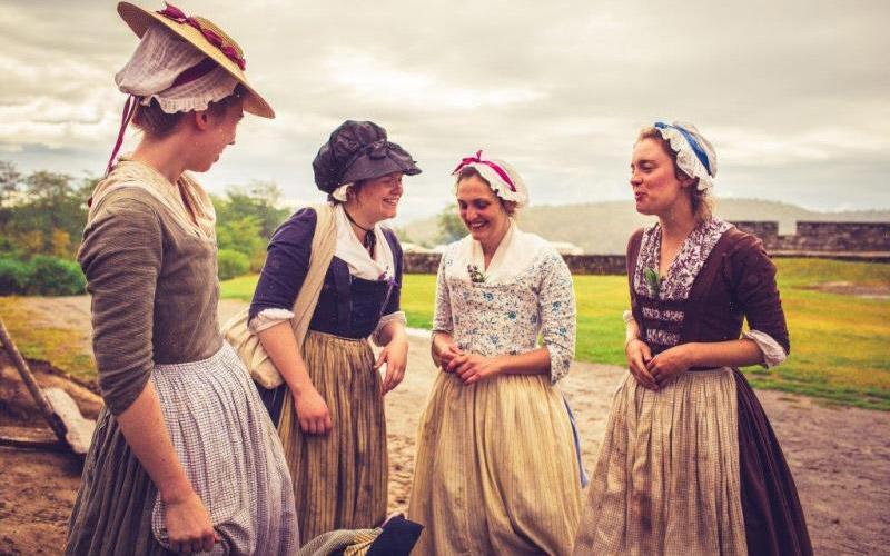 Women re-enactors in period clothing standing in field