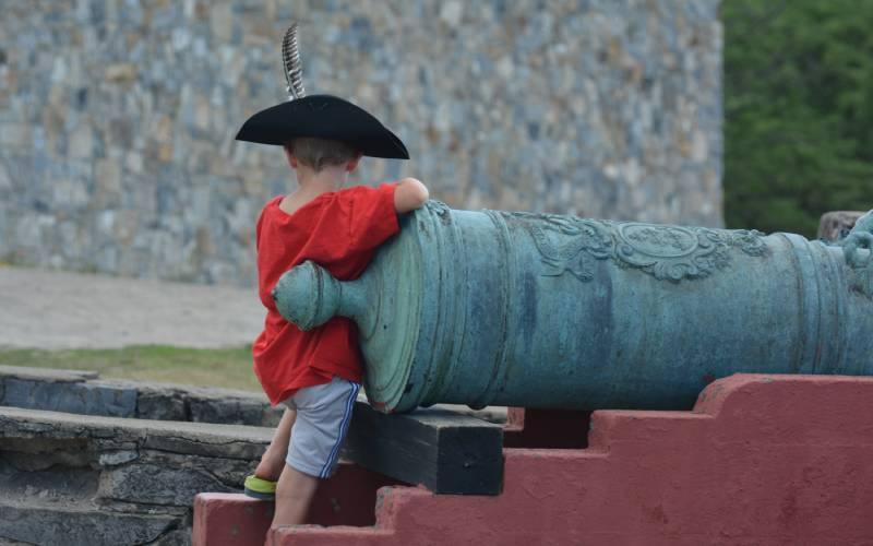 boy wearing hat on cannon