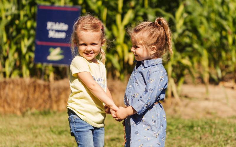 Little girls in front of corn maze