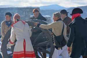 historic interpreters moving a cannon in the snow