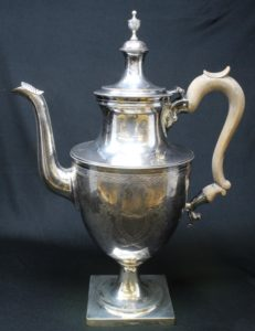 The silver coffeepot mentioned in Mary Channing Gibbs' estate papers. The urn shape of the vessel and engraved decorations that resemble laurel wreaths are classical elements of the Federal style.