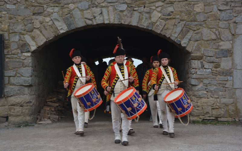 fife and drum players in red and yellow uniforms
