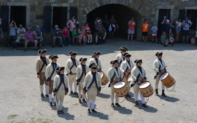 fifers and drummers playing in front of crowd on fort parade ground
