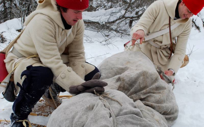 historical interpreters outside preparing items to snowshoe